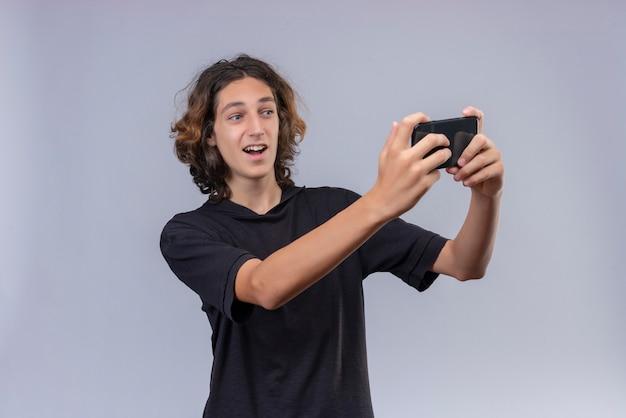 Lächelnder kerl mit langen haaren im schwarzen t-shirt machen ein selfie auf weißer wand