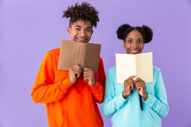 Lächelnder kerl und mädchen, die bücher halten und lesen, lokalisiert über violetter wand