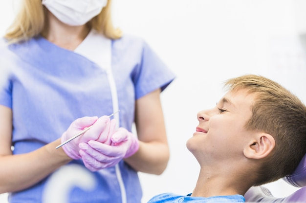 Lächelnder kinderpatient vor dem weiblichen zahnarzt, der skalator hält