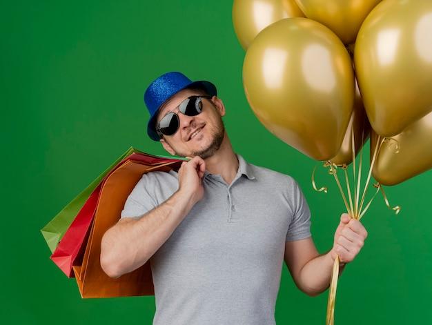 Lächelnder kippender junger party-typ, der partyhut und brille trägt, die geschenktüten auf schulter setzen und ballons lokalisiert auf grün halten