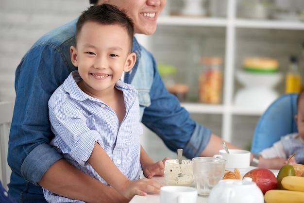 Lächelnder kleiner junge am frühstück mit familie