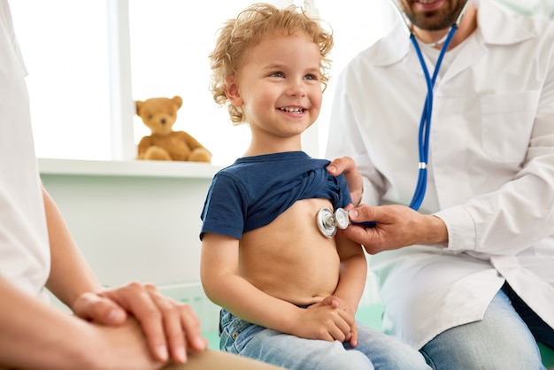 Lächelnder kleiner junge bei der medizinischen untersuchung
