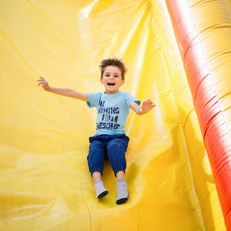 Lächelnder kleiner junge, der auf aufblasbarer rutsche spielt