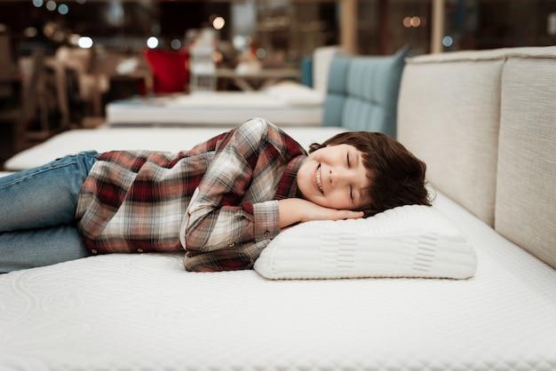 Lächelnder kleiner junge, der auf bett im matratzenspeicher liegt