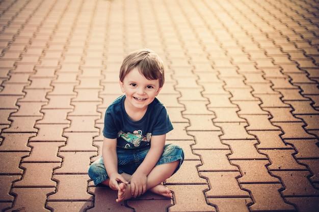 Lächelnder kleiner junge, der auf dem boden sitzt