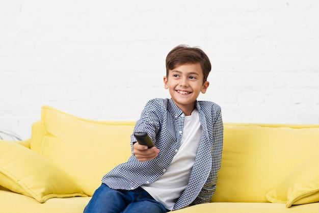 Lächelnder kleiner junge, der auf sofa stationiert
