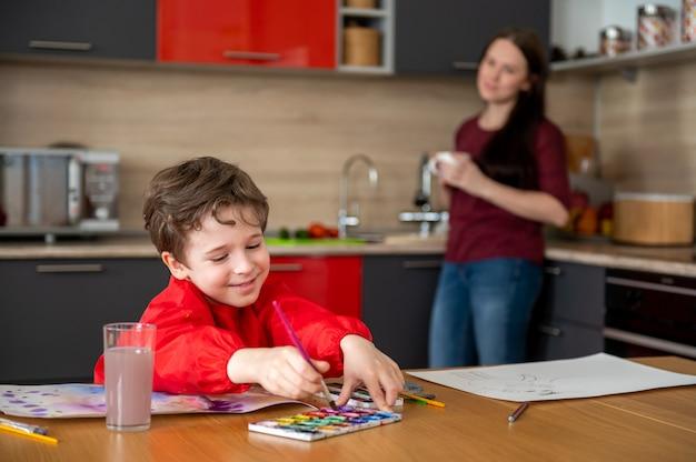 Lächelnder kleiner junge, der bilder auf küche mit mutter zeichnet