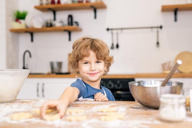 Lächelnder kleiner junge, der dich ansieht, während er eines der rohen kekse auf den tisch nimmt, während er seiner mutter hilft
