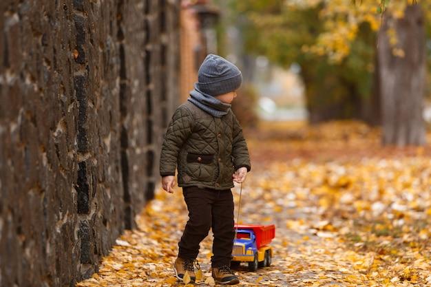 Lächelnder kleiner junge, der draußen mit dem spielzeugauto im herbst geht und spielt. glückliche kindheit konzept. lustiges kinderporträt