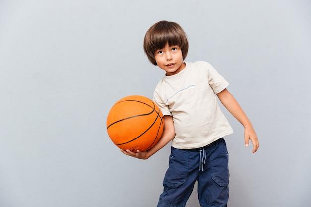 Lächelnder kleiner junge, der mit basketballball steht und spielt