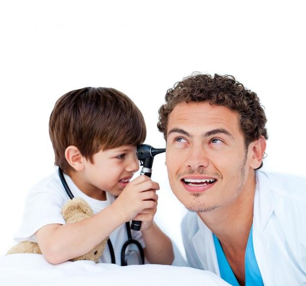 Lächelnder kleiner junge, der mit dem doktor spielt