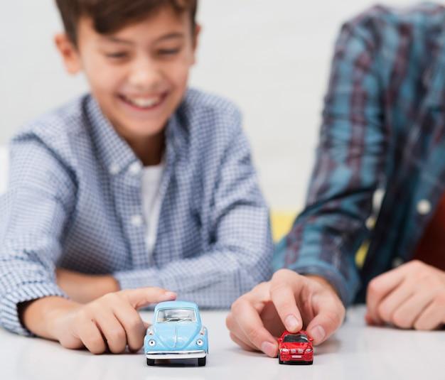 Lächelnder kleiner junge, der mit spielzeugautos spielt