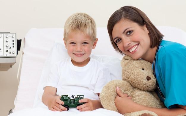 Lächelnder kleiner junge, der woth seinen doktor spielt