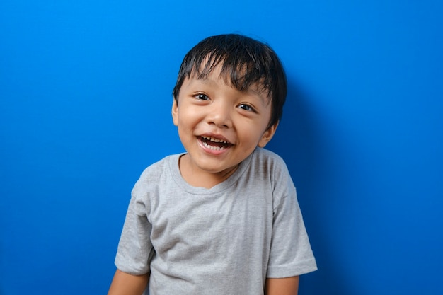 Lächelnder kleiner junge im grauen t-shirt, kamera isoliert auf blauem wandhintergrund suchend, studioportrait. menschen religiöses lifestyle-konzept.