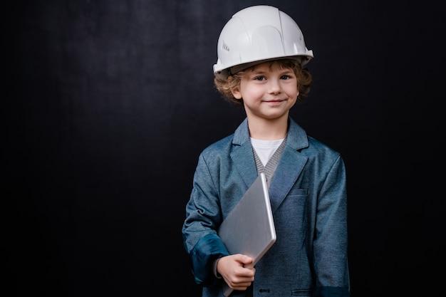 Lächelnder kleiner junge im helm und in der abendgarderobe, der gefalteten laptop hält, während er isoliert gegen schwarzen raum steht