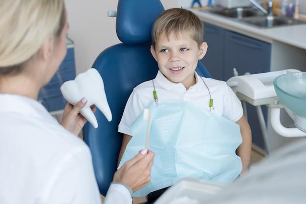 Lächelnder kleiner junge im zahnarztstuhl
