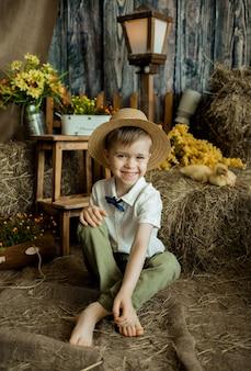Lächelnder kleiner junge in einem strohhut sitzt mit entenküken im stroh. osterferien