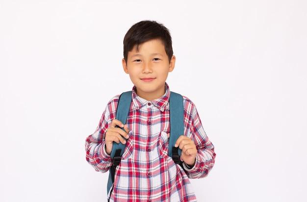 Lächelnder kleiner junge in schuluniform mit großem rucksack