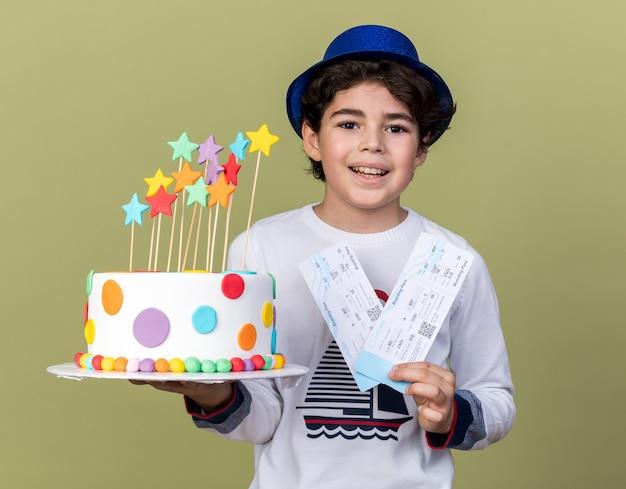 Lächelnder kleiner junge mit blauem partyhut, der tickets mit kuchen hält