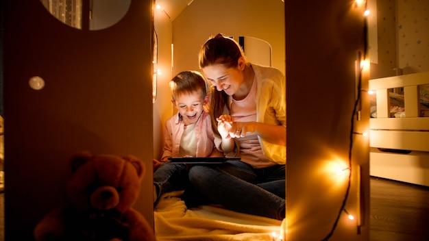 Lächelnder kleiner junge mit mutter, die im spielzeugpappehaus spielt und tablet-computer verwendet. konzept der kindererziehung und der familie, die nachts zeit zusammen haben.