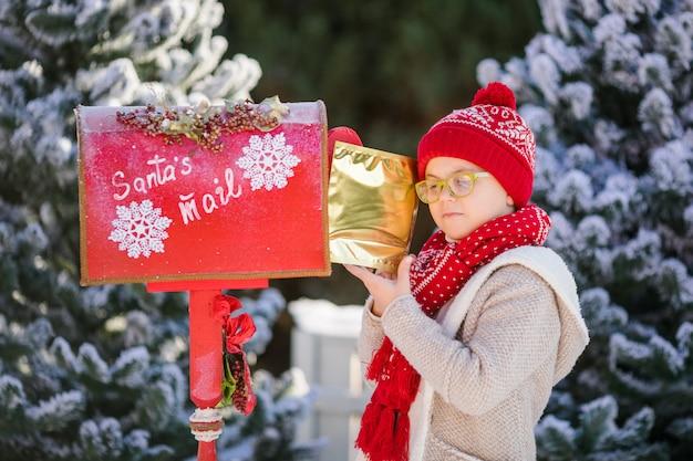 Lächelnder kleiner junge mit rotem hut und grünen gläsern mit seinem brief nahe dem briefkasten des sankt
