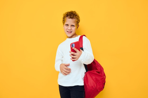 Lächelnder kleiner junge mit rotem rucksack ruft am gelben hintergrund des telefons an