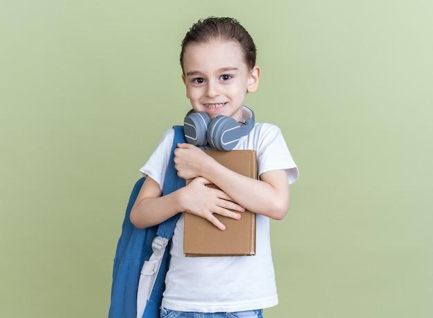 Lächelnder kleiner junge mit rucksack und kopfhörern um den hals, der ein buch hält und umarmt