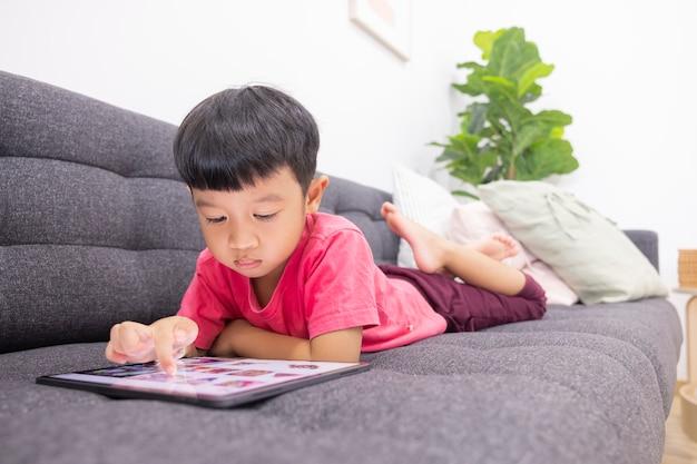 Lächelnder kleiner junge schaut auf das touchpad, das auf einem bequemen sofa im wohnzimmer liegt