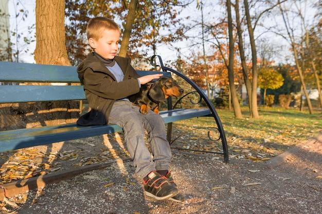 Lächelnder kleiner junge und hund, die auf bank im herbstpark sitzen