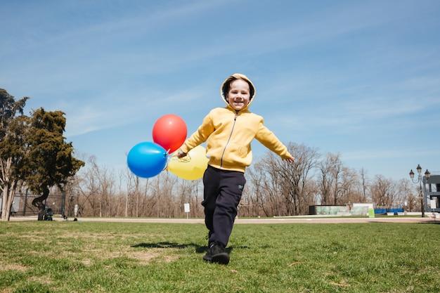 Lächelnder kleiner kinderjunge, der draußen im park mit luftballons geht