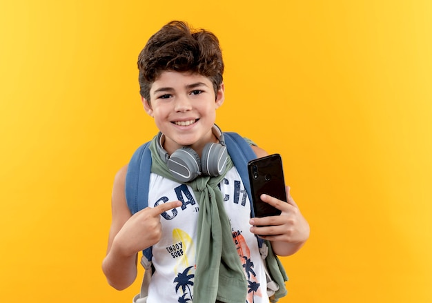 Lächelnder kleiner schuljunge, der rückentasche und kopfhörer hält und auf telefon lokalisiert auf gelber wand hält