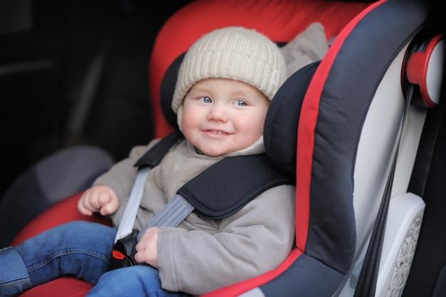 Lächelnder kleinkindjunge, der im autositz sitzt