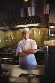 Lächelnder koch, der mit verschränkten armen in der gewerblichen küche steht