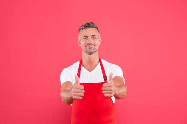 Lächelnder kochmann zeigt daumen nach oben. kochprofi gesucht. männlicher chefkoch in roter schürze. geschäftsmann trägt schürze im café. sein lieblingswerk. porträt des hübschen berufskochs. am besten vom besten.