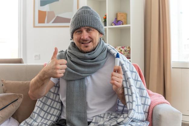 Lächelnder kranker mann mit schal um den hals, der eine wintermütze trägt, die in plaid gehüllt ist, ein thermometer hält und auf der couch im wohnzimmer sitzt