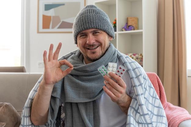 Lächelnder kranker mann mit schal um den hals, der eine wintermütze trägt, die in plaid gewickelt ist, die medizin-blisterpackungen hält und ein ok-schild auf der couch im wohnzimmer gestikuliert