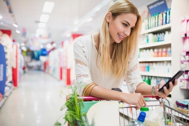Lächelnder kunde, der ihr telefon am supermarkt aufpasst
