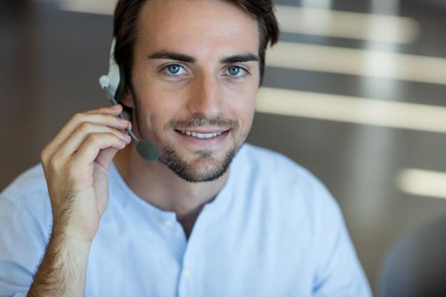 Lächelnder kundendienst, der über kopfhörer im büro spricht