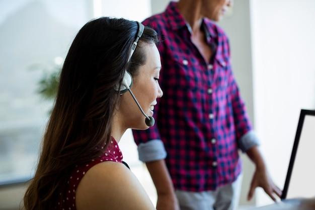 Lächelnder kundendienstmitarbeiter, der im büro arbeitet