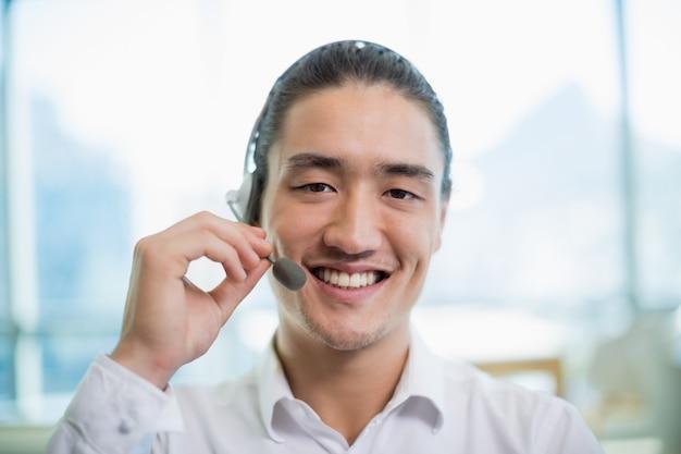 Lächelnder kundendienstmitarbeiter, der im call center arbeitet