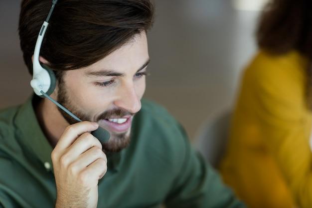 Lächelnder kundendienstmitarbeiter, der über kopfhörer im büro spricht