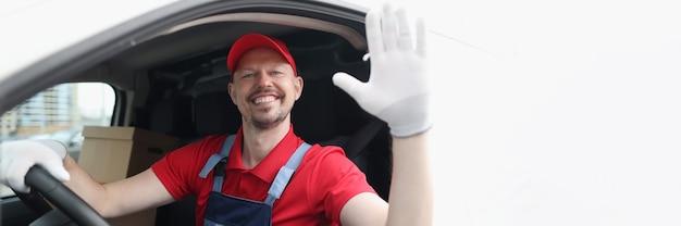 Lächelnder kurierfahrer in der autokabine winkt mit der hand zur begrüßung