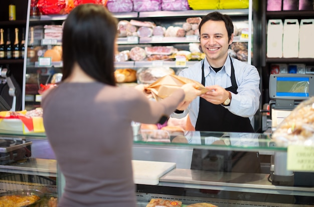 Lächelnder ladenbesitzer, der einen kunden bedient
