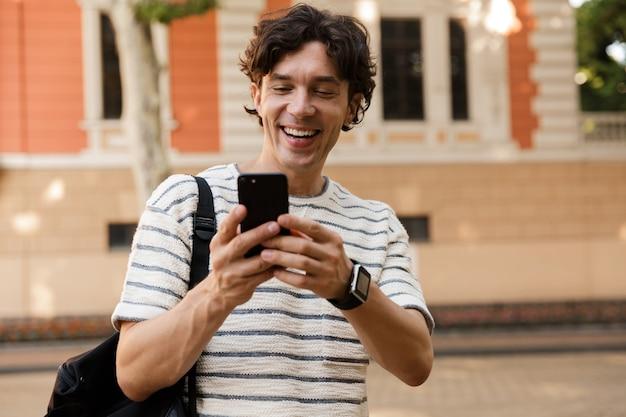 Lächelnder lässiger mann, der rucksack an der stadtstraße trägt