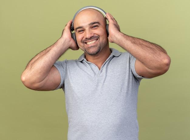 Lächelnder lässiger mann mittleren alters mit kopfhörern, der die hände auf ihnen hält und nach vorne auf olivgrüne wand schaut
