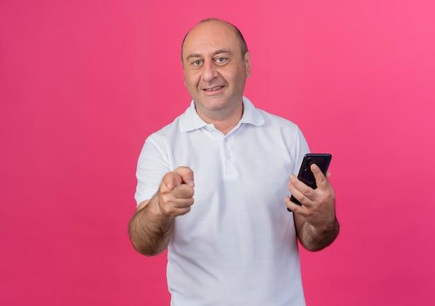 Lächelnder lässiger reifer geschäftsmann, der handy hält und auf kamera lokalisiert auf rosa hintergrund mit kopienraum zeigt