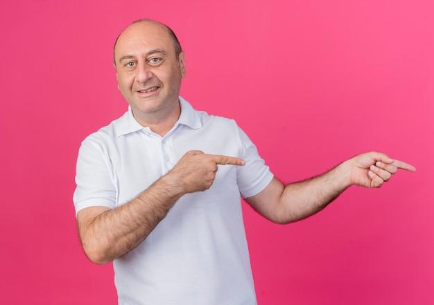 Lächelnder lässiger reifer geschäftsmann, der kamera betrachtet, die auf seite lokalisiert auf rosa hintergrund zeigt