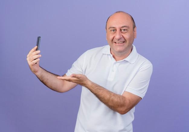 Lächelnder lässiger reifer geschäftsmann, der kamera hält und mit der hand auf handy lokalisiert auf lila hintergrund betrachtet