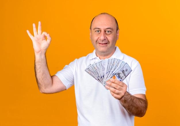 Lächelnder lässiger reifer mann, der bargeld hält und okey geste zeigt, die auf gelber wand lokalisiert wird