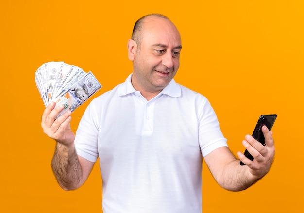 Lächelnder lässiger reifer mann, der bargeld hält und telefon in seiner hand lokalisiert auf gelber wand betrachtet